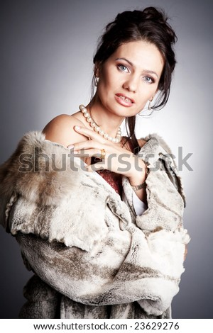 Luxurious woman wearing fur and a necklace - stock photo