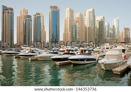 Luxurious Yachts and Boats in Front of Dubai Marina Skyscrapers, in the daylight. All the logos and trade names are removed from the picture. - stock photo