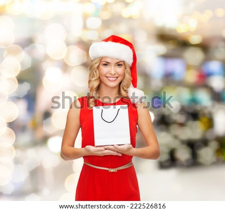 luxury, advertisement, holydays and sale concept - smiling woman in santa helper hat with white blank shopping bag over lights background - stock photo