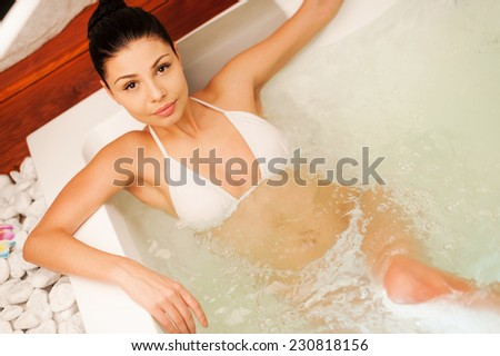 Luxury bath. Top view of attractive young woman relaxing in hot tub and looking at camera - stock photo