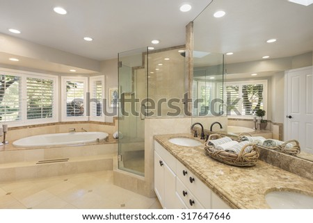 Luxury bathroom with marble tiles,  glass shower and oval bathtub. - stock photo