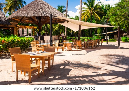Luxury beach resort on Caribbean sea in Dominican Republic, cozy cafe on white sandy coast, beautiful big palm trees, enjoying day spa, summer holidays concept - stock photo