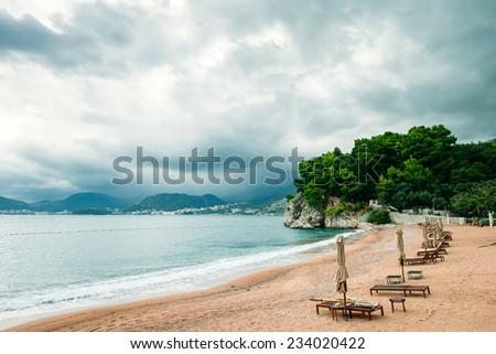 luxury beach resort with sunbeds and umbrellas with rainy sky / beach resort with rainy sky - stock photo