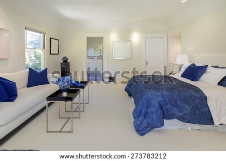 Luxury bedroom in expensive blue tones ans couch. - stock photo