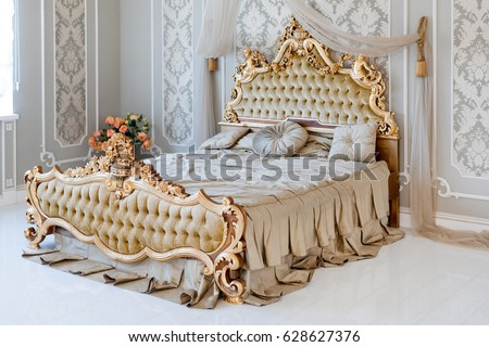 luxury bedroom in light colors with golden furniture details big comfortable double royal bed in