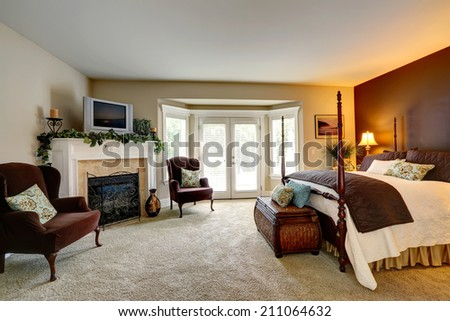 Luxury bedroom with fireplace. View of beautiful bed with high poles and antique chest - stock photo