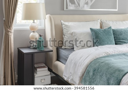 luxury bedroom with green color tone and classic lamp on table side - stock photo