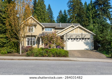 Luxury beige house with beautiful landscaping on a suburban street. Home exterior design. - stock photo