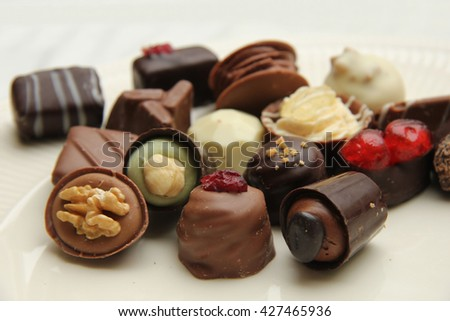 Luxury belgium chocolate pralines, decorated with fruits and nuts - stock photo