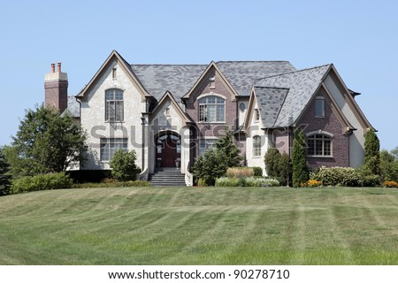 Luxury brick and stone home with arched entry - stock photo