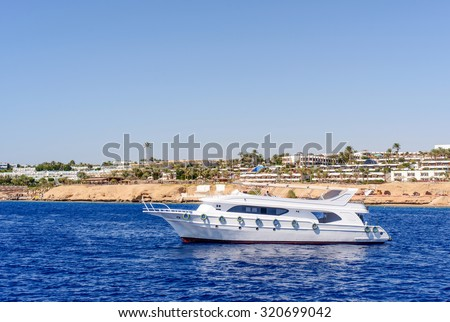 Luxury cabin cruiser cruising offshore parallel to the coastline and a tropical resort on a sunny summer day enjoying their vacation - stock photo