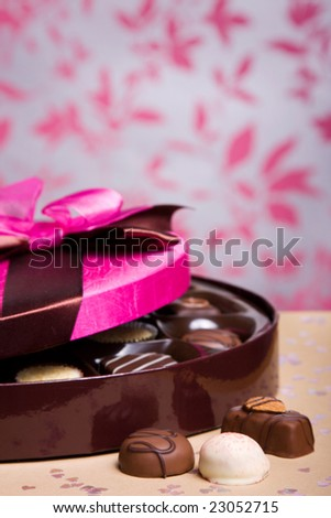 Luxury chocolates with a pink satin lid, shallow depth of field with focus on chocolates at front - stock photo