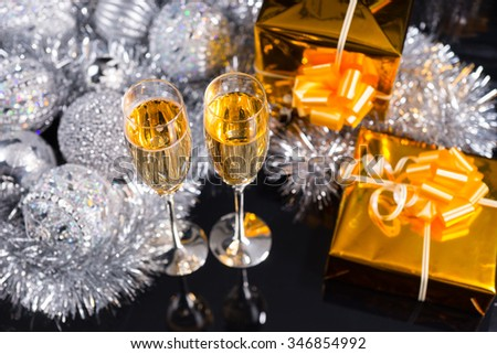 Luxury Christmas still life with two flutes of sparkling champagne, decorated gold gifts and an arrangement of silver tinsel and Xmas decorations viewed high angle on a black background