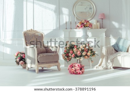 luxury clean bright white interior. a spacious room with sunlight and flowers in vases,