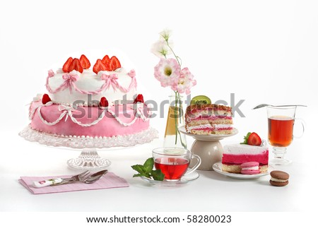 Luxury composition with a pie, tea, fruit cakes and flowers. Sweets from a confectioner's shop on a birthday party.