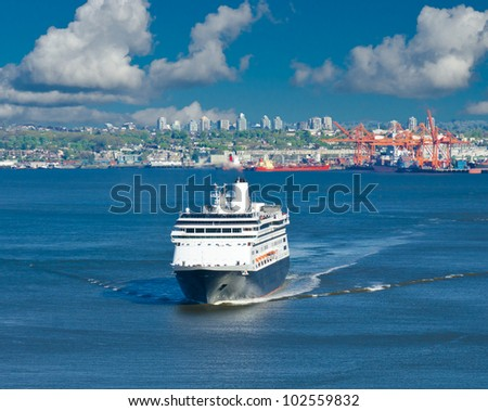 Luxury cruise ship sailing ( arriving ) from port Vancouver in a sunny day with bright clouds.  Canada. - stock photo