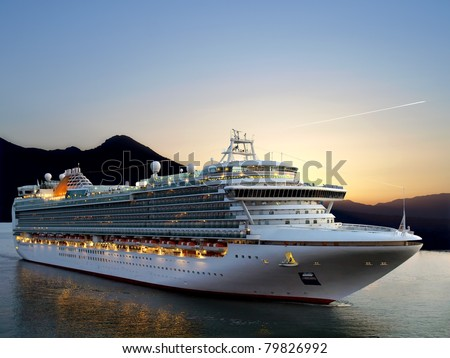 Luxury cruise ship sailing from port on sunrise. - stock photo