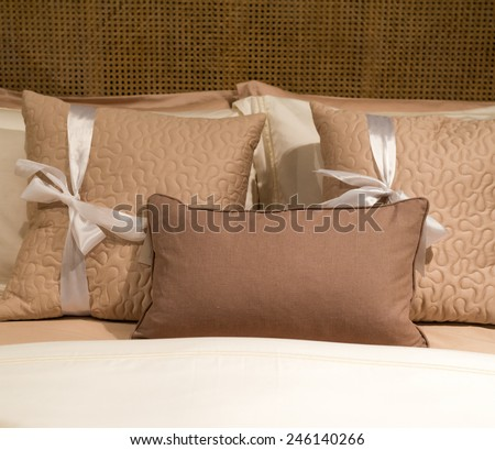 Luxury Cushions on Bed in Various Shades of Brown with RIbbon - stock photo