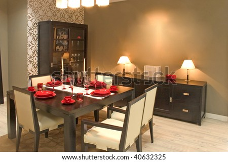 Luxury dining room and dinig table with glasses, dishes and furniture. - stock photo