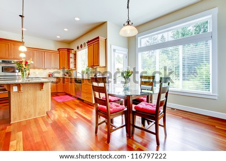 Luxury Dining room and kitchen with red cherry wood and large window. - stock photo