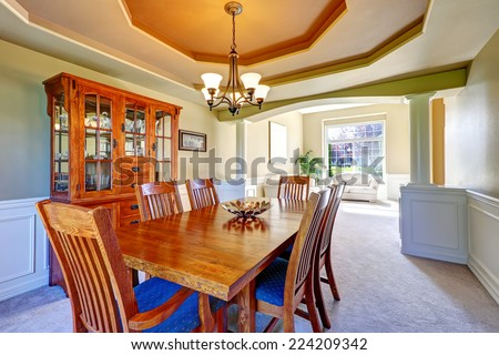 Luxury dining room with white columns and olive walls. Coffered ceiling and carpet floor