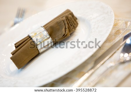 Luxury dining table setting with white plates, fork, knife and spoon with napkin on white table with selective focus. - stock photo