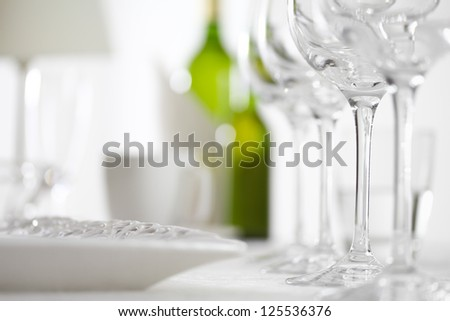 Luxury elegant dinner table setting in restaurant or hotel with wine glasses and white wine - stock photo