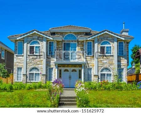 Luxury family house with landscaping and blue sky background - stock photo
