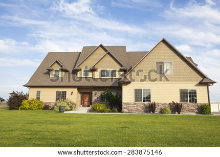 luxury family house with landscaping on the front and blue sky on background
