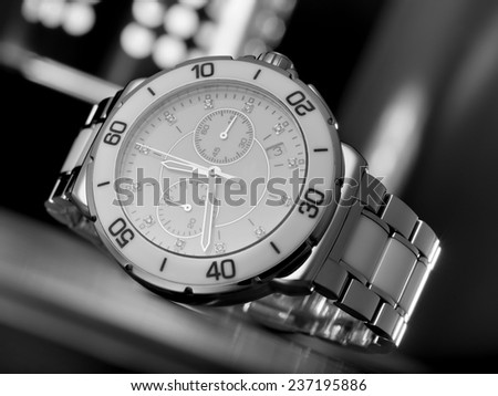Luxury female wristwatch on the table in front of abstract background, diagonal studio closeup with selective focus - stock photo