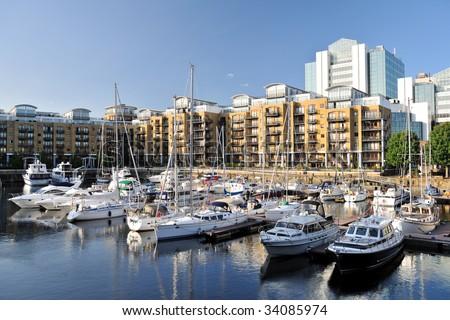 Luxury flats, City Quay, and yachts moored in the east dock marina, St Katherine Dock, London, England, UK, Europe - stock photo