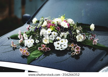 Luxury floral decorations of asters and roses on a black car of newlyweds. - stock photo