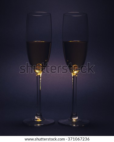Luxury glasses with wine, studio isolated on purple background.