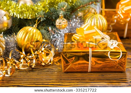 Luxury gold themed Xmas background wit a decorative gift in gold foil with matching golden baubles on a pine branch - stock photo