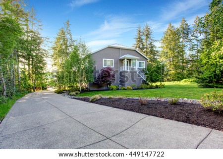 Luxury gray house with white trim and two garage spaces with concrete floor driveway. - stock photo