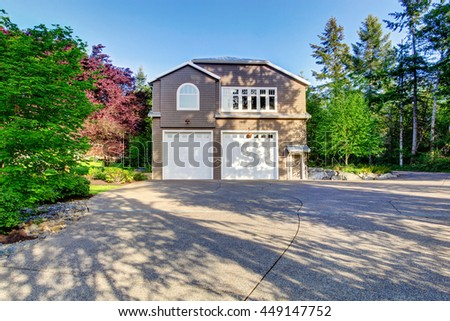 Luxury gray house with white trim and two garage spaces with concrete floor driveway and beautiful landscape design. - stock photo