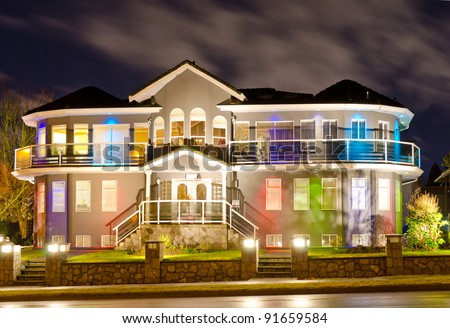 Luxury home exterior in the night time with the lights - stock photo