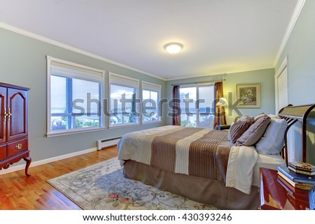 Luxury home master bedroom with many windows. blue walls, large brown bed and hardwood floor. - stock photo