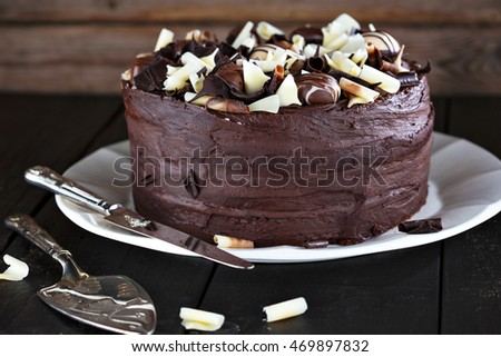 Luxury homemade chocolate cake with shovel and cutting knife on dark brown wooden table.
