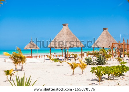 Luxury hotel at tropical resort on ocean shore with palm trees - stock photo