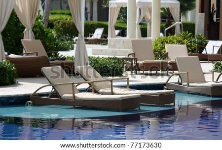 luxury hotel resort pool, chairs and patio - stock photo