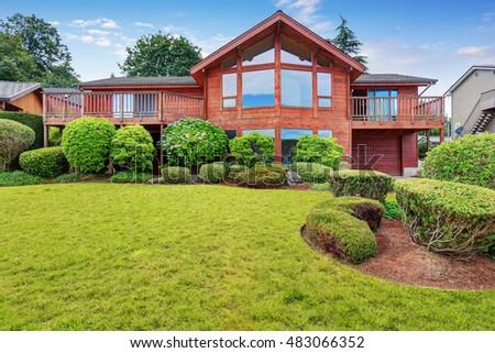luxury house exterior with wooden panel trim garage and well kept garden around northwest