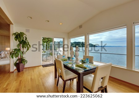 Luxury house interior. Bright elegant dining area with glass wall and  scenic bay view. Room has exit to walkout deck