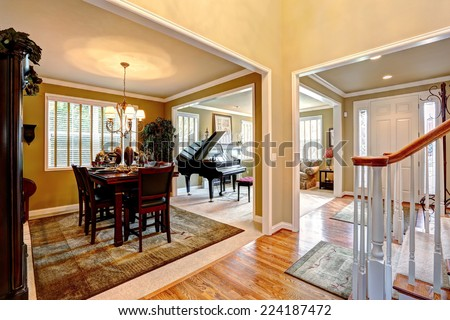 Luxury house interior with open floor plan. Dining area and living room with grand piano - stock photo