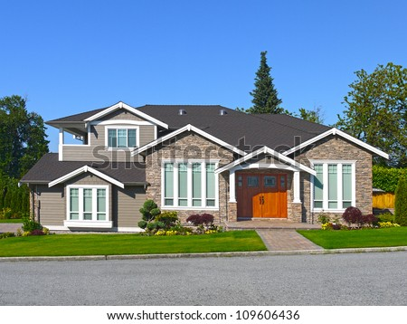 Luxury house with blue sky and lush landscape - stock photo