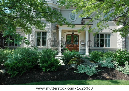 Luxury house with manicured green garden in front - stock photo