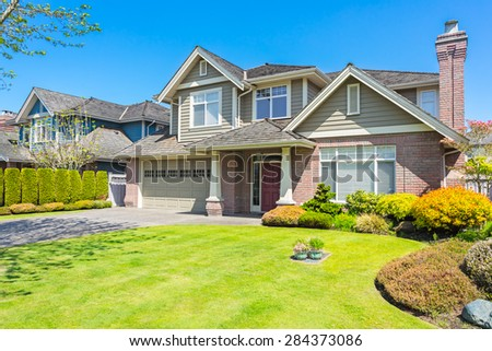 Luxury house with nicely trimmed and designed front yard, lawn in a residential neighbourhood in Canada.  - stock photo