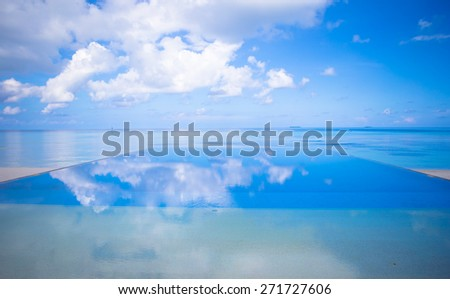 Luxury infinity swimming pool in the tropical hotel - stock photo
