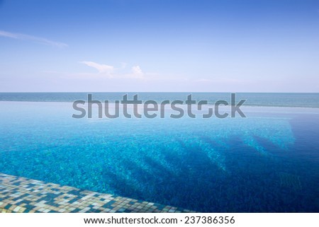 Luxury Infinity swimming pool with blue sky - stock photo