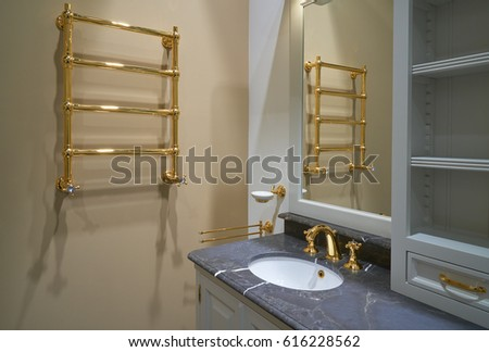 Luxury Interior bathroom with gold painted faucet and heated towel rail